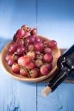 Verres de vin rouge avec des raisins rouges et une bouteille de vin sur le bleu Image libre de droits