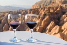Verres de vin rouge sur le fond rouge de vallée dans Cappadocia La Turquie Photo stock