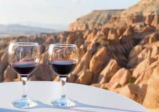 Verres de vin rouge sur le fond rouge de vallée dans Cappadocia La Turquie Photos libres de droits