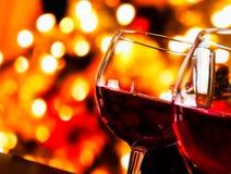 Verres de vin rouge sur le fond unfocused coloré de lumières Photographie stock libre de droits