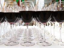 Verres de vin rouge sur le plan rapproché blanc de table Photographie stock
