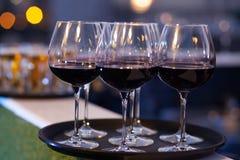 Verres de vin rouge sur le plateau Photos stock