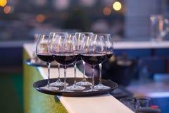 Verres de vin rouge sur le plateau Images stock