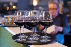 Verres de vin rouge sur le plateau noir Images stock