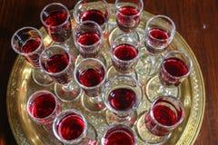 Verres de vin rouge sur un plateau d'or image stock