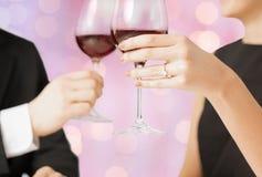 Verres de vin tintants engagés heureux de couples Image libre de droits
