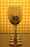 Verres de vin vides transparents un derrière l'autre et fond jaune-orange avec les taches blanches image libre de droits