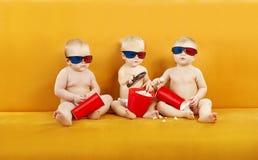 Verres du bébé 3D observant le film à TV, enfants mangeant du maïs éclaté et Photos stock