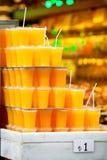 Verres en plastique avec le jus d'orange Photographie stock