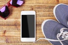 Verres, espadrilles et smartphone Image stock