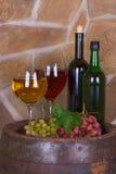 Verres et bouteilles de vin, fromage sur le vieux baril Images libres de droits