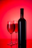 Verres et bouteilles de vin rouge sur le rouge Images libres de droits