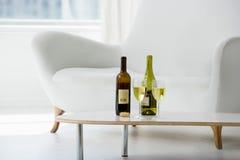 Verres et bouteilles de vin sur la table basse Photos libres de droits