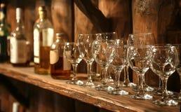 verres et bouteilles de vin sur une étagère rétro Photo libre de droits