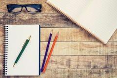 Verres et carnet avec le stylo placé sur une table en bois Photographie stock libre de droits