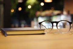 Verres et carnet de plan rapproché au café de café lecture et travail images libres de droits