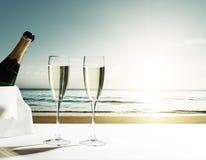 Verres et coucher du soleil de champagne sur la plage Photos stock