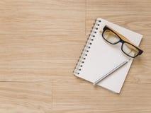 Verres et crayon d'oeil de carnet sur le plancher en bois photographie stock