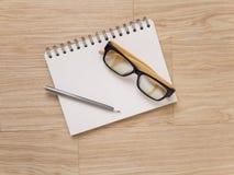 Verres et crayon d'oeil de carnet sur le plancher en bois images libres de droits