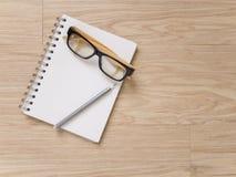 Verres et crayon d'oeil de carnet sur le plancher en bois Images stock