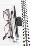 Verres et gomme de crayon de carnet sur le fond blanc Photos libres de droits