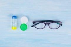 Verres et objets pour nettoyer et stocker des verres de contact, pour améliorer la vision, sur un fond bleu Photos libres de droits