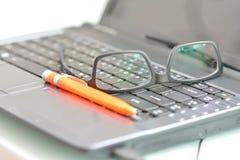 Verres et stylo sur l'ordinateur portable au bureau Images stock