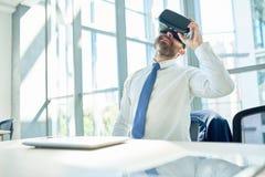 Verres mûrs d'Using VR d'homme d'affaires dans le bureau images libres de droits