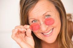 Verres mûrs décontractés heureux de rouge de femme Images libres de droits