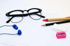 Verres noirs, livre blanc, crayon, stylo, affûteuse rose, gomme Photo stock