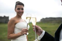 Verres nuptiales de tintement de couples de champagne Photographie stock