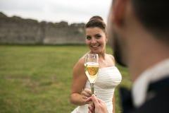 Verres nuptiales de tintement de couples de champagne Photo stock