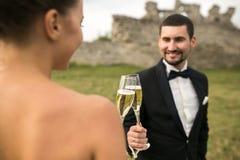 Verres nuptiales de tintement de couples de champagne Images stock