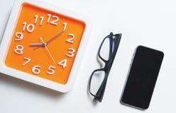 Verres oranges modernes d'horloge et téléphone intelligent photos stock