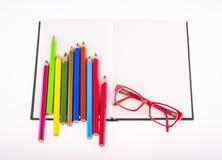 Verres rouges et crayons de couleur placés sur le carnet Photos stock
