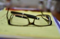 Verres, stylo, carnet et pour faire la liste photographie stock libre de droits