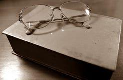 Verres sur la sépia de vieux livre Photo stock