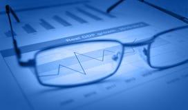 Verres sur le diagramme et le graphique financiers bleus, concept de succès Images stock