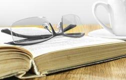 Verres sur le livre et une tasse de café Photographie stock libre de droits