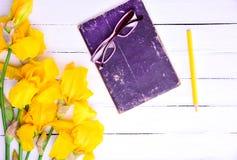 Verres sur un livre, à côté d'un bouquet des iris jaunes Images stock