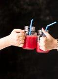 Verres tintants de personnes avec le smoothie de pastèque Photographie stock libre de droits