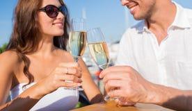 Verres tintants de sourire de champagne de couples au café Photographie stock libre de droits