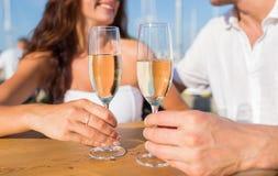 Verres tintants de sourire de champagne de couples au café Photographie stock