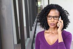 Verärgerte AfroamerikanerGeschäftsfrau, die am Handy spricht Lokalisiert auf Bürogebäude mit Kopienraum Lizenzfreies Stockbild