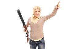 Verärgerte Frau, die ein Gewehr hält und mit dem Finger zeigt Lizenzfreie Stockfotografie