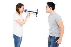 Verärgerte Frau, die am jungen Mann auf Hornlautsprecher schreit Stockfotos