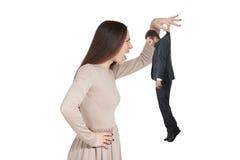 Verärgerte Frau, die kleinen Mann hält Stockfoto