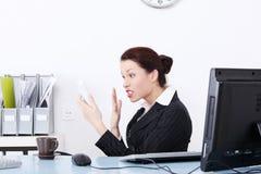 Verärgerte Geschäftsfrau, die zum Telefon schreit. Stockfoto