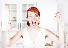 Verärgerte Hausfrau mit Nudelholz Stockbilder