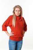 Verärgerte junge blonde Frau mit den Händen auf dem Anstarren beider Hüften Stockfoto